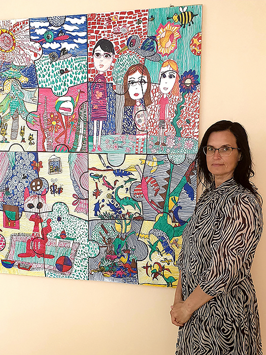 Dovilų pagrindinės mokyklos specialioji pedagogė S. Venckienė– prie autizmo sutrikimų turinčių vaikų piešto paveikslo.